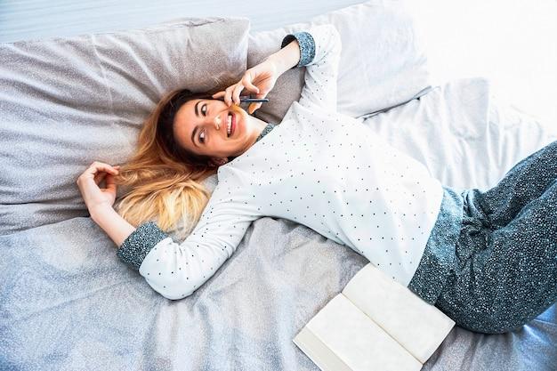 Młoda kobieta przebywa w sypialni rozmawia przez telefon