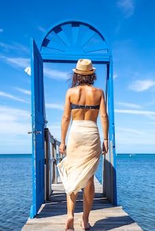 Młoda kobieta przechodząca przez niebieskie drzwi na drewnianym chodniku na karaibskiej wyspie roatan w hondurasie, zdjęcie pionowe