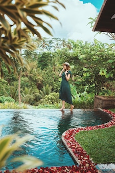 Młoda kobieta przechodzi przez otwarty prywatny basen z widokiem na tropikalną dżunglę na bali
