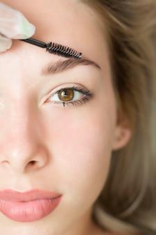 Młoda kobieta przechodzi zabieg korekcji brwi, barwienia henną, laminowania. zbliżenie. połowa twarzy
