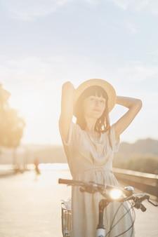 Młoda kobieta przeciw natury tłu z rowerem