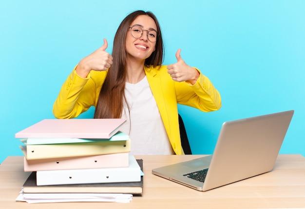 Młoda kobieta przed biznesem uśmiechnięta szeroko, wyglądająca na szczęśliwą, pozytywną, pewną siebie i odnoszącą sukcesy, z kciukami do góry