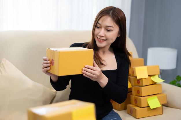 Młoda kobieta przedsiębiorca przygotowuje paczkę w biurze domowym