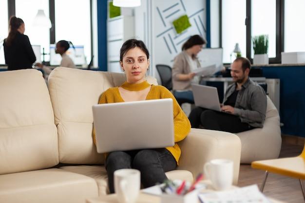 Młoda kobieta przedsiębiorca siedzi na kanapie w środku biznesu uruchamia biuro patrząc na kamerę uśmiechając się trzymając laptopa