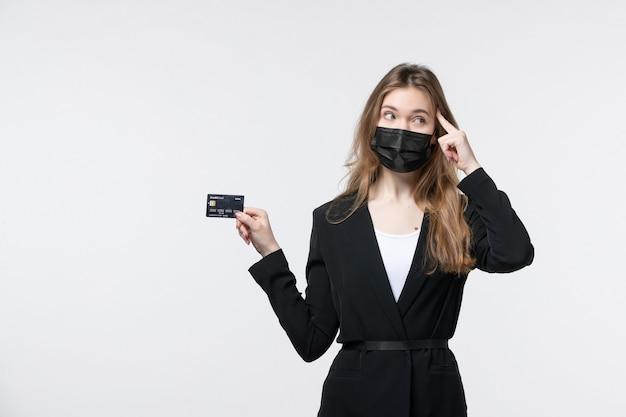 Młoda kobieta przedsiębiorca w garniturze, ubrana w maskę medyczną i trzymająca kartę bankową w głębokich myślach na białej ścianie