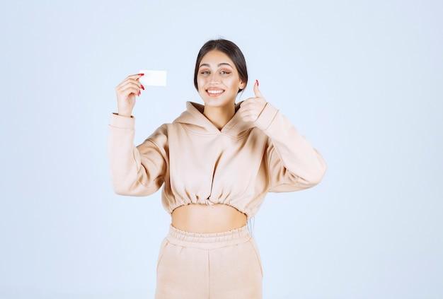 Młoda kobieta przedstawia swoją wizytówkę i pokazuje dobry znak