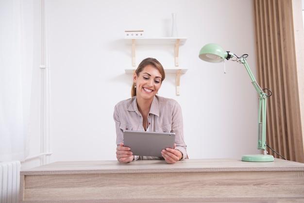 Młoda kobieta przegląda internet na jej tablecie