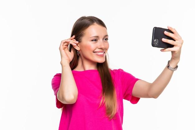 Młoda kobieta przeglądania w smartfonie lub ma połączenie wideo na białym tle