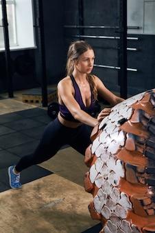 Młoda kobieta przerzucanie opon w siłowni