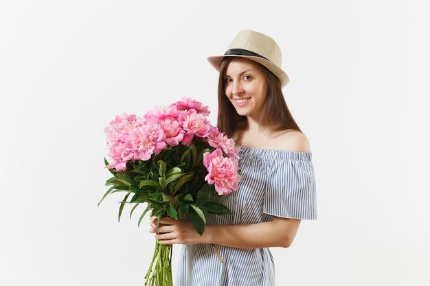 Młoda kobieta przetargu w niebieską sukienkę, kapelusz trzymając bukiet kwiatów piękne różowe piwonie na białym tle. dzień świętego walentego, koncepcja wakacje międzynarodowy dzień kobiet. powierzchnia reklamowa.