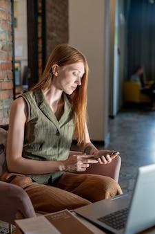 Młoda kobieta przewijanie w smartfonie siedząc w fotelu