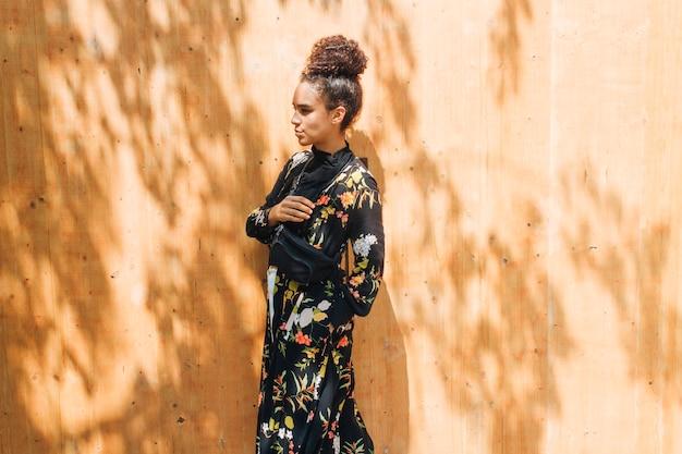 Młoda kobieta przewożących talii torby stojącej na zewnątrz ściany