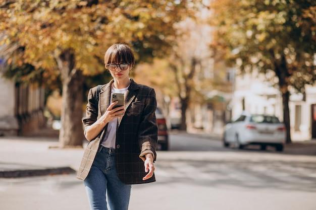 Młoda kobieta przez jezdnię i przy użyciu telefonu