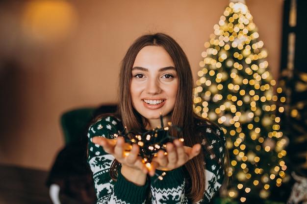Młoda kobieta przy choinką z bożonarodzeniowe światła jarzyć się