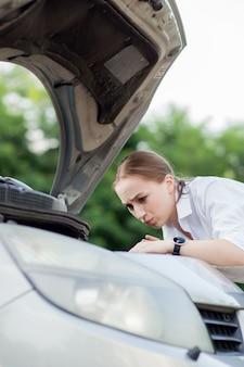 Młoda kobieta przy drodze po tym, jak jej samochód się zepsuł. otworzyła maskę, by zobaczyć uszkodzenia
