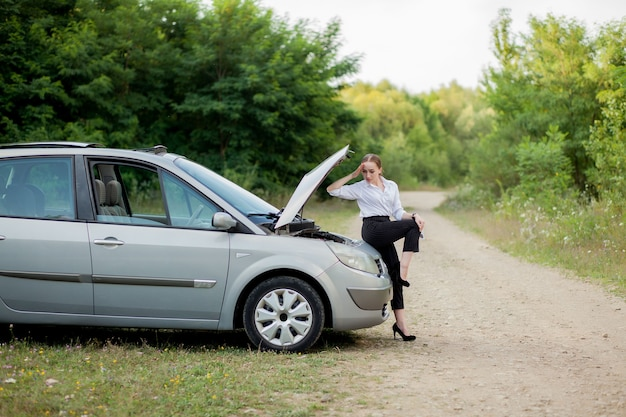 Młoda kobieta przy drodze po zepsuciu samochodu. otworzyła maskę, aby zobaczyć uszkodzenia.