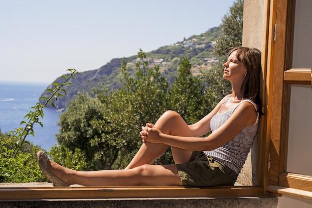 Młoda kobieta przy dużym otwartym okno.