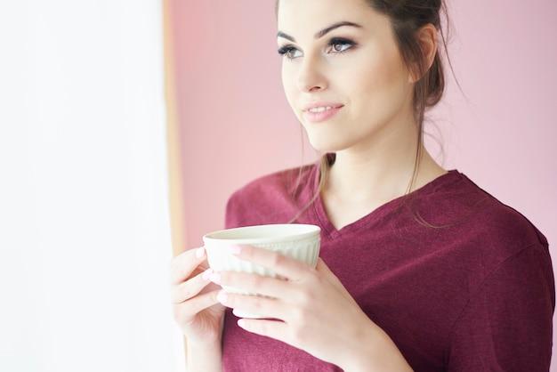 Młoda kobieta przy filiżance kawy rano