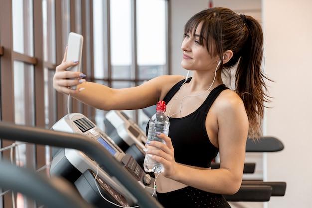 Młoda kobieta przy gym bierze selfie