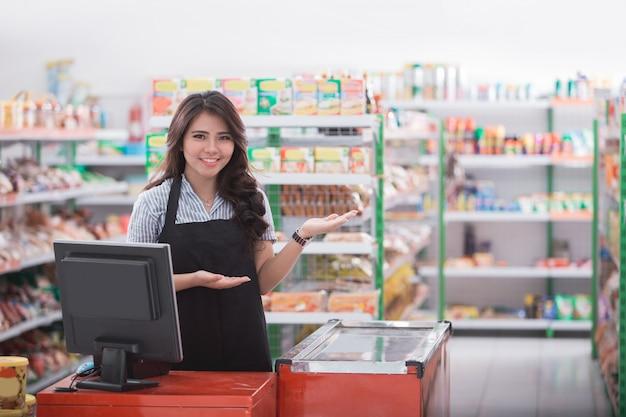 Młoda kobieta przy kasą w sklepie wita klienta