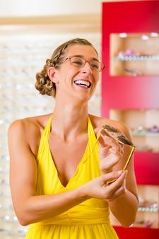 Młoda kobieta przy okulistą z szkłami