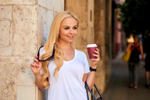 Młoda kobieta przy ścianą na ulicie z kawą