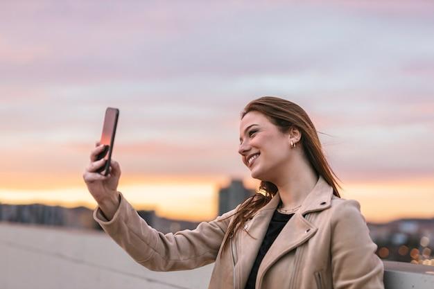 Młoda kobieta przy selfie z jej telefonu komórkowego