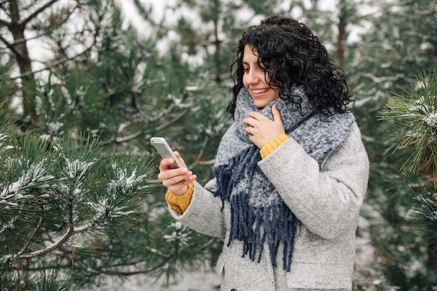 Młoda kobieta przy użyciu swojego telefonu komórkowego w śnieżnym zimowym parku. koncepcja gadżetów ludów.