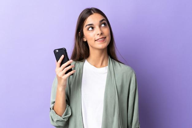 Młoda kobieta przy użyciu telefonu komórkowego na białym tle na fioletowej ścianie patrząc w górę podczas uśmiechu