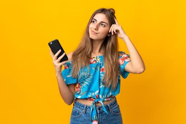 Młoda kobieta przy użyciu telefonu komórkowego na izolowanych żółtej ścianie ma wątpliwości iz niejasnym wyrazem twarzy