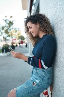 Młoda kobieta przy użyciu telefonu komórkowego, stojąc na zewnątrz na ulicy. koncepcja urbanistyczna.