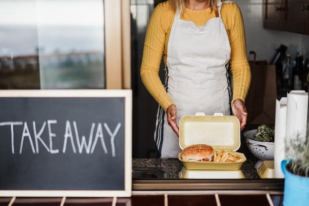 Młoda kobieta przygotowuje fast food na wynos w restauracji kuchennej - skup się na rękach trzymających pakiet