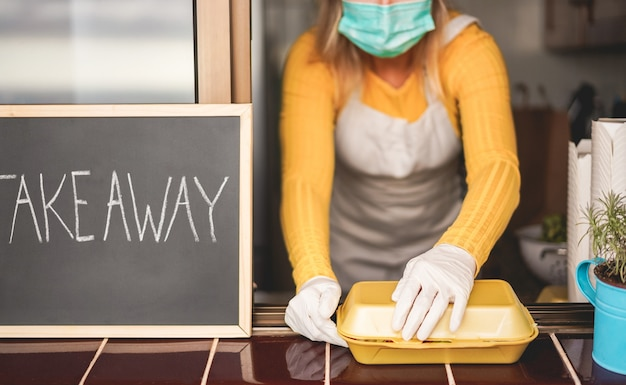 Młoda kobieta przygotowuje jedzenie na wynos w restauracji w czasie epidemii koronawirusa