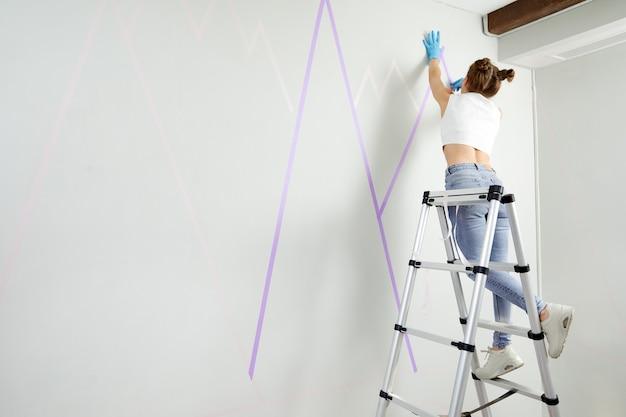 Młoda kobieta przygotowuje ścianę do malowania stojąc na drabinie projekt diy