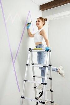 Młoda kobieta przygotowuje ścianę do malowania stojąc na drabinie, stosując taśmę maskującą na projekcie ściennym diy