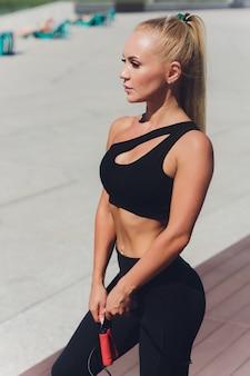 Młoda kobieta przygotowuje się do uprawiania sportów na świeżym powietrzu na nowoczesnej promenadzie w pobliżu swojego zespołu apartamentów.