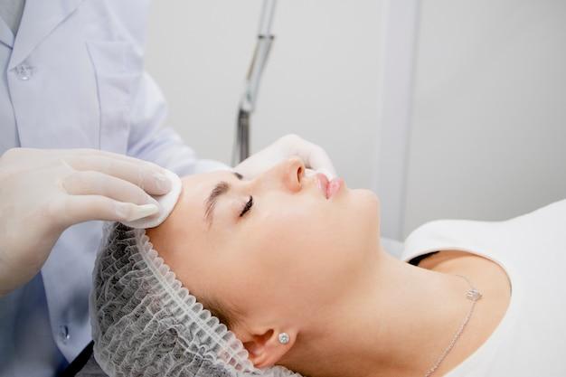 Młoda kobieta przygotowuje się i oczyszcza skórę, aby była gotowa do zabiegu w salonie kosmetycznym.