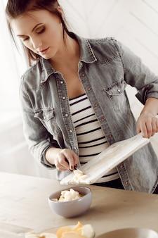 Młoda kobieta przygotowuje śniadanie w kuchni