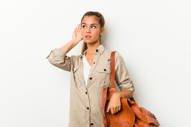 Młoda kobieta przygotowywająca dla podróży próbuje słuchać plotki