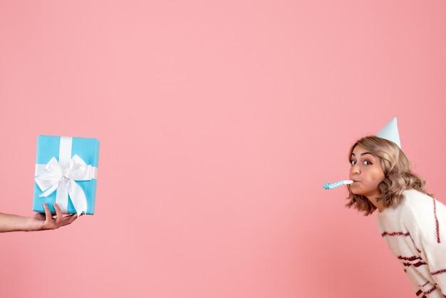 Młoda kobieta przyjmuje prezent od mężczyzny na różowo