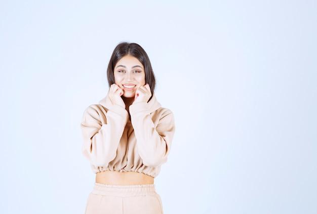 Młoda kobieta przykładając rękę do twarzy i słuchając z radością
