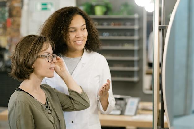 Młoda kobieta przymierza nowe okulary przed lustrem, podczas gdy dziewczyna rasy mieszanej udziela jej rady podczas konsultacji