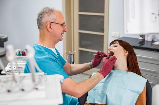 Młoda kobieta przyszła do dentysty siedzącego na fotelu z otwartymi ustami. starszy uśmiechnięty mężczyzna dentysta sprawdza jej zęby. szczęśliwy pojęcie pacjenta i dentysty.