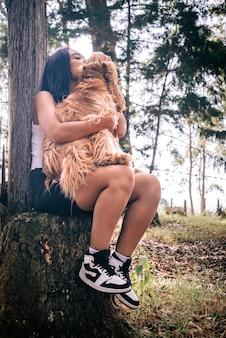 Młoda kobieta przytula i całuje swojego psa, odpoczywając na krześle w kształcie drzewa