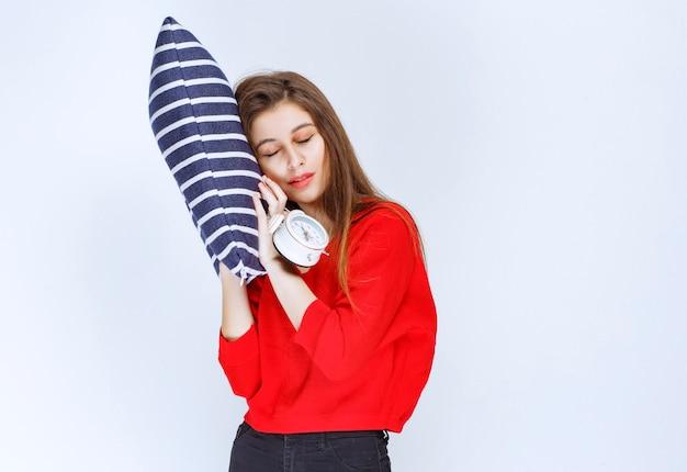 Młoda kobieta przytula poduszkę w niebieskie paski, budzik i spanie.
