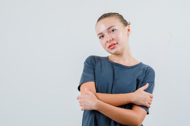 Młoda kobieta przytula się w szarej koszulce i wygląda z nadzieją