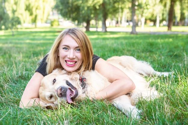 Młoda kobieta przytula swojego psa retrievera, leżąc na trawie. koncepcja miłości zwierząt