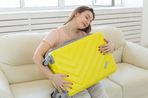Młoda kobieta przytulanie jej żółtą walizkę
