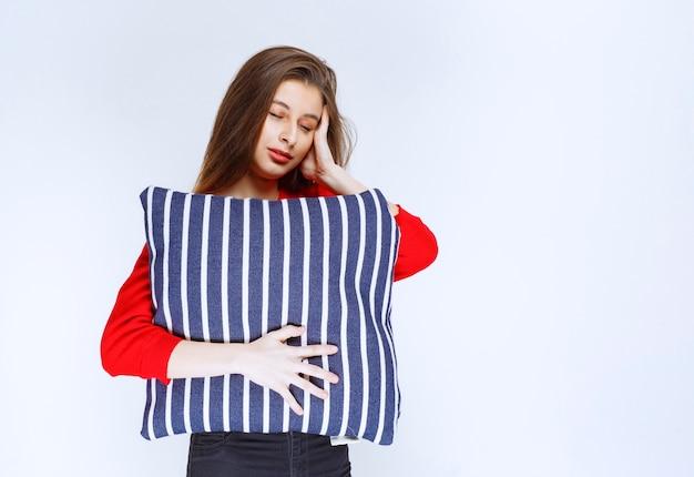 Młoda kobieta przytulanie poduszkę w niebieskie paski i spanie.