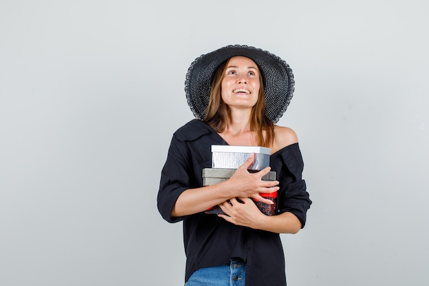 Młoda kobieta przytulanie pudełka na prezenty, patrząc w koszulę, spodenki, kapelusz i patrząc wesoło